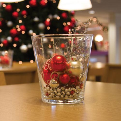 Donkergroen kerstboomservice kerstarrangementen glaswerk gevuld met decoratie